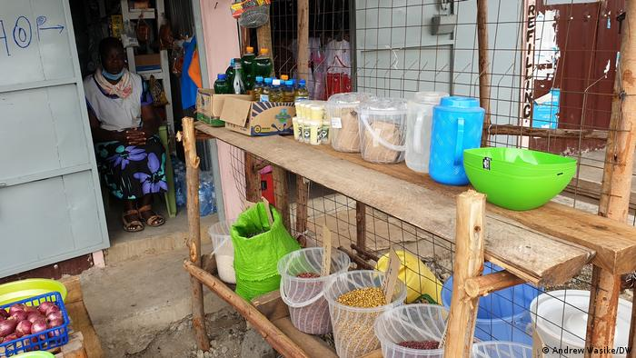 Plastic buckets filled with legumes and grains in wooden shelves in a small shop