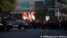 Police line up to block protesters carrying a large banner of Aung San Suu Kyi
