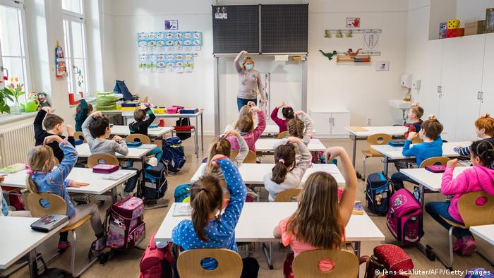 First graders of the 39th Dresden primary school sit in their classroom for the first lesson following the coronavirus lockdown in Dresden, eastern Germany, on February 15, 2021