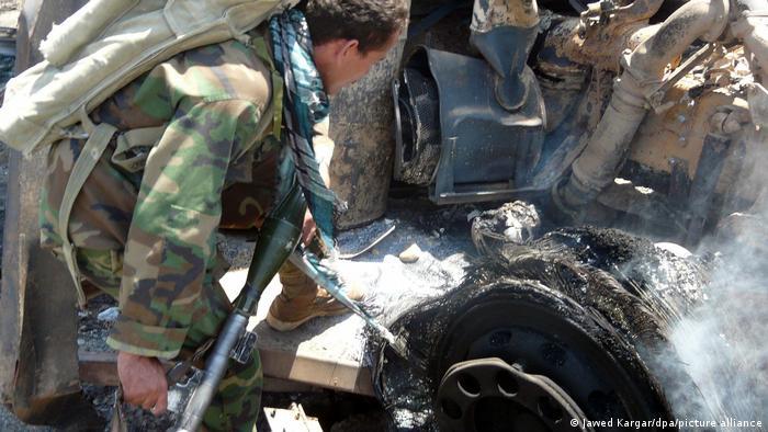 Afganistanski vojnik pored spaljene cisterne