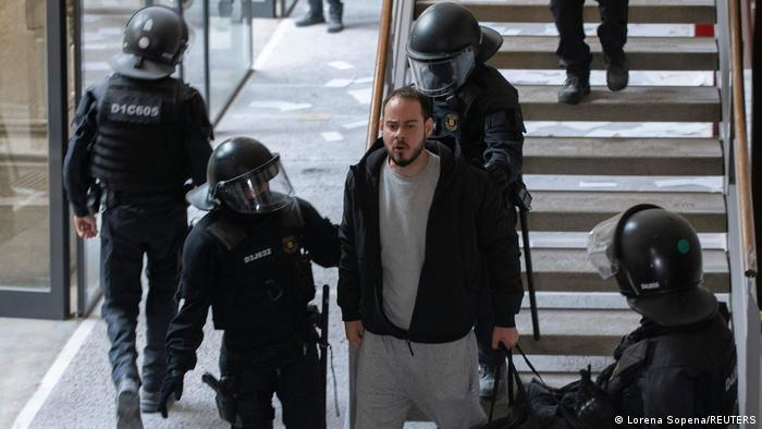 Riot police detain rapper Pablo Hasel near some stairs inside the university. Hasel is wearing gray jogging pants and t-shirt and a black hoody
