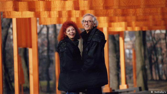 Christo and Jeanne-Claude stand together in black coats, in front of an orange backdrop.