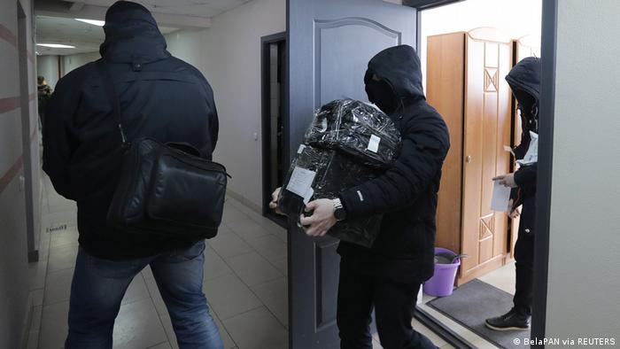 Law enforcement officers wearing all black and hoods leave the office of the independent Belarusian Association of Journalists carrying objects wrapped in black film