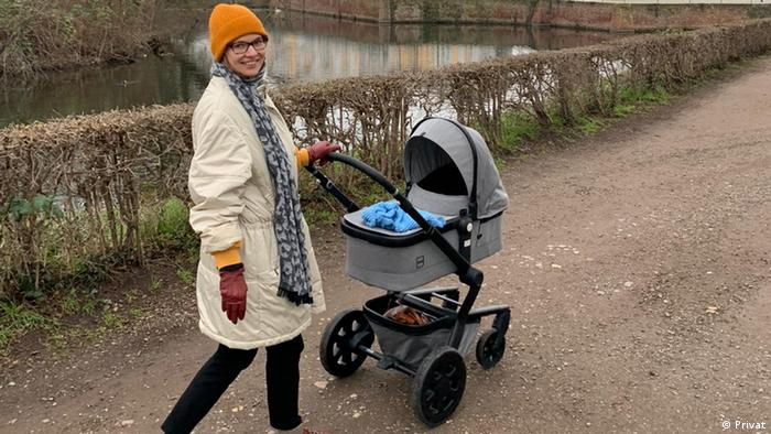 A mother pushing her baby in a pram