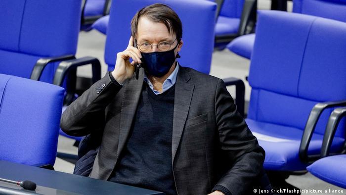 Karl Lauterbach takes a call in the German parliament