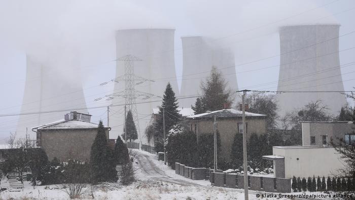 Rauch steigt aus großen Schornsteinen im Hintergrund, vorne sind Häuser. Bäume und Stromleitungen zu sehen, alles ist mit Schnee bedeckt