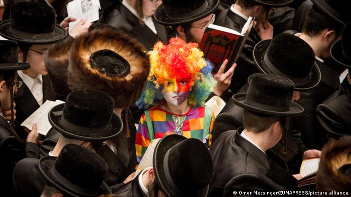 Ultra Orthodox Jews are reading from the Book of Esther with a child costumed as a clown in the center of the photo