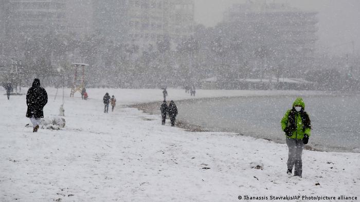 Άνθρωποι που περπατούν στη χιονισμένη παραλία στην Αθήνα