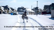 A man walks to his friend's home in a neighbourhood without electricity as snow covers the BlackHawk neighborhood in Pflugerville, Texas, U.S. February 15, 2021. Picture taken February 15, 2021. Bronte Wittpenn/Austin American-Statesman/USA Today Network via REUTERS. NO RESALES. NO ARCHIVES. MANDATORY CREDIT TPX IMAGES OF THE DAY