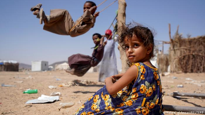 A girl sits as other children play on swings at a camp for internally displaced people in Marib, Yemen