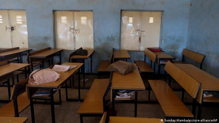 School bags sit on wooden desks in an empty school classroom