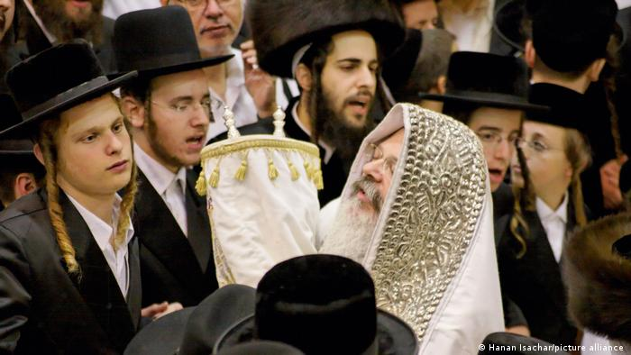 A Rabbi carrying Torah scrolls surrounded by Jewish men