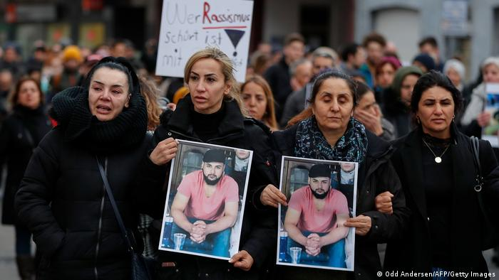 People hold up photos of victims during a march following a vigal outside a shisha cafe in Hanau near Frankfurt am Main, western Germany, on February 21, 2020