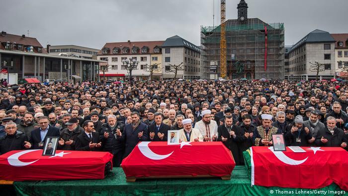 Multidão diante de caixões cobertos com a bandeira da Turquia