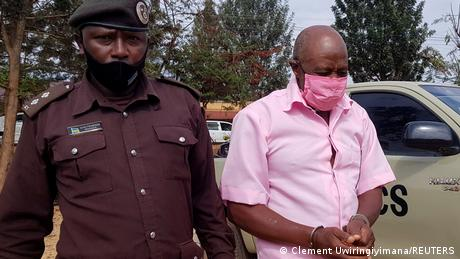 Paul Rusesabagina is pictured in handcuffs accompanied by the police