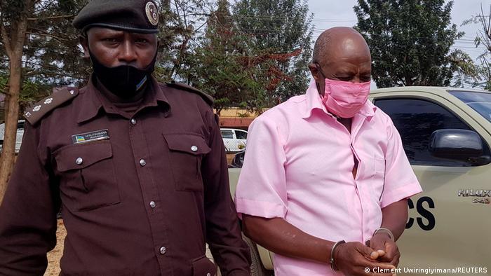 Ativista ruandense Paul Rusesabagina algemado acompanhado por policial