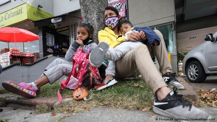 Madre e hijos esperan ayuda en una calle de Bogotá