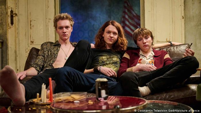 Drei Jugendliche sitzen auf einer Couch. Vor ihnen auf einem Tisch steht das Fixer-Geschirr aus Kerzen. Es handelt sich um eine Filmszene aus Wir Kinder vom Bahnhof Zoo.