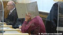 A man covers his face with a file in court