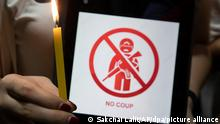 A hand holding a candle and a piece of paper that says no coup.