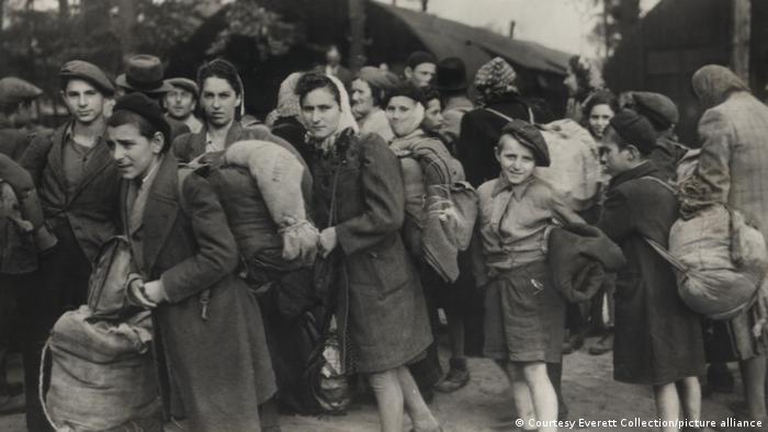 Erwachsene und Kinder mit Bündeln stehen gedrängt, einige schauen in die Kamera, es sind jüdische Passagiere eines Schiffes, die 1947 nach Palästina einwandern wollten, aber zurück nach Lübeck gebracht wurden