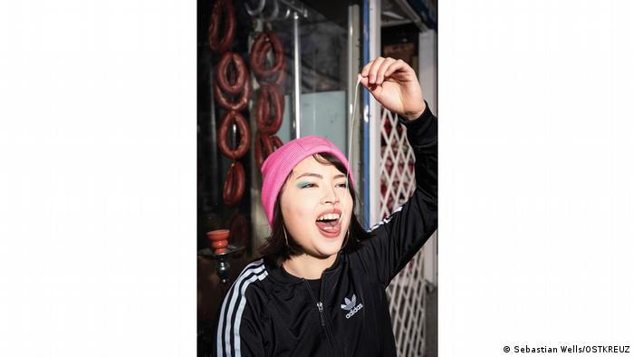 Comedian Erika Ratcliffe zieht einen Kaugummi aus dem Mund nach oben in die Länge.