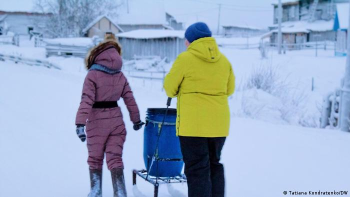 Two locals push a sled with a water barrel through the snow