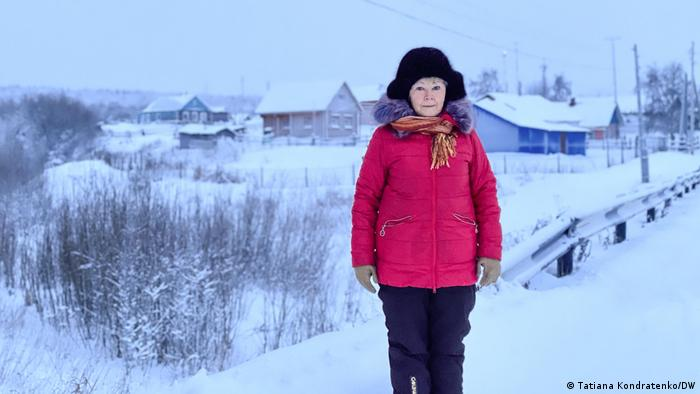 A woman stands in the snow with a Russian village in the background