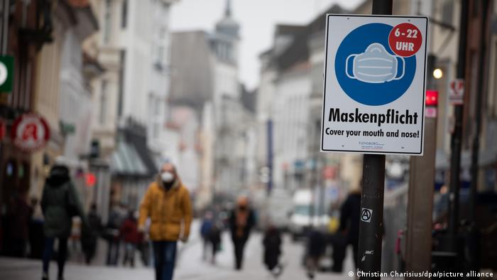 Pedestrians walk in the center of Flensburg wearing masks, near a sign advising mask protection from COVID-19