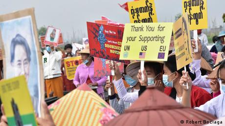 Myanmar protesters holding signs