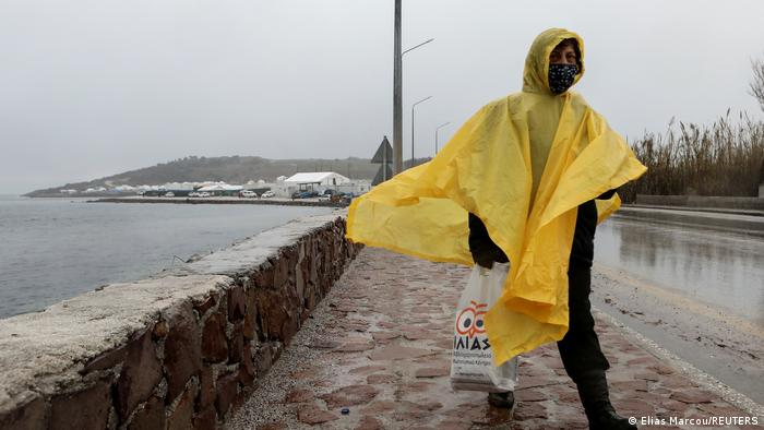 Woman walking in a yellow rain cape along a sidewalk with Kara Tepe camp in the background