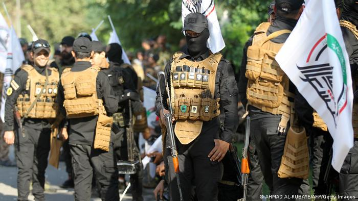 Members of Iraqi paramilitary holding guns and flags, stand guard during a funerary procession in Baghdad.