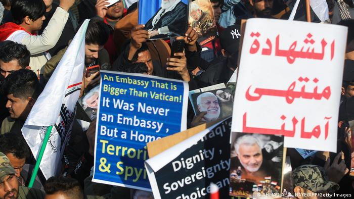 Iraqi demonstrators hold placards at a rally marking one year since the killing of the two commanders in a US drone strike