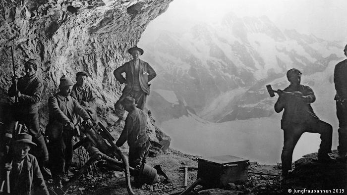 Historical photograph of the construction of the Jungfrau Railway line (black and white): men hammering the tunnel into the rock with tools