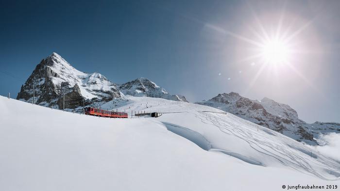 Switzerland, Alps, a train heading through snow towards the valley, the Junfraujoch peak in the background