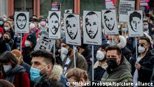 People hold pictures of the nine victims during a demonstration on the market square in Hanau, Germany, Frankfurt, Feb. 19, 2021. One year ago a far right man shot nine people before he shot himself. (AP Photo/Michael Probst)