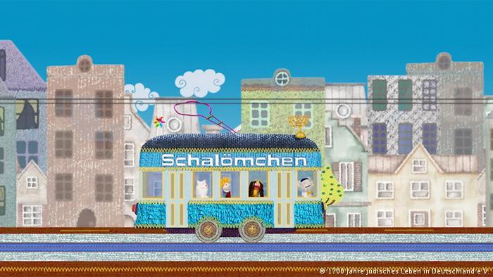 Puppen sitzen in einem blauen Bus, auf dem Schalömchen steht.
