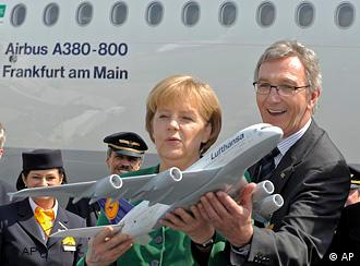Wolfgang Mayrhuber, Chairman and CEO of Deutsche Lufthansa, right, and German Chancellor Angela Merkel hold a mock up of an Airbus A380 aircraft in front of the Airbus A380 'Frankfurt am Main'