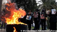 Relatives of victims of the Aug. 4, 2020 Beirut port explosion hold portraits of their loved one who killed during the explosion, as they burn tires to block a road during a sit-in outside the Justice Palace, in Beirut, Lebanon, Friday, Feb. 19, 2021. The prosecutor investigating last year's massive blast in Beirut was formally notified Friday that he would no longer lead an enquiry into last year's deadly port explosion, state-run Lebanon's National News Agency reported. (AP Photo/Bilal Hussein)