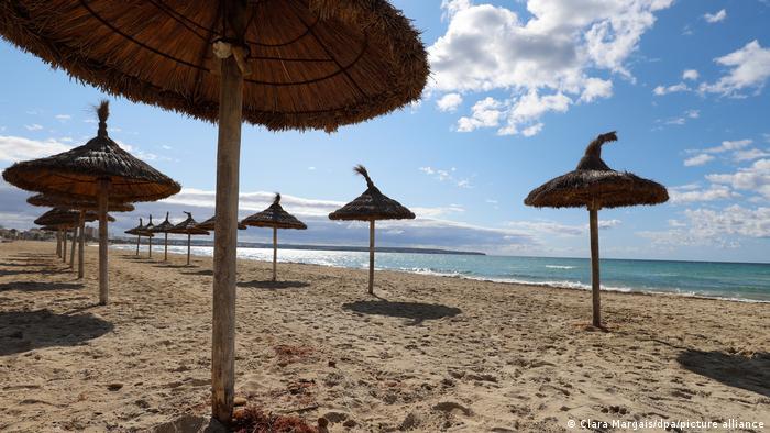 Spain - Mallorca - an empty beach with wicker parasols