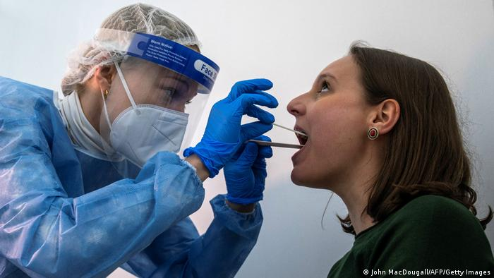 Nurse in protective gear taking a swab from the back of a woman's throat