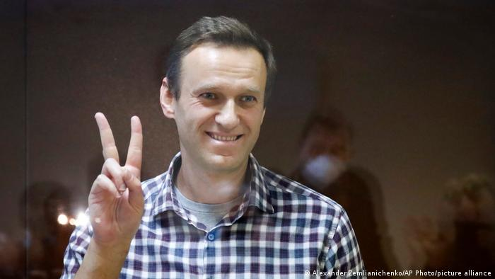 Alexei Navalny makes a peace sign while in court in Moscow, Russia