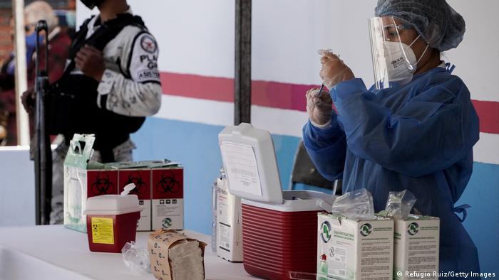 Foto de una persona que prepara una dosis de la vacuna contra el coronavirus
