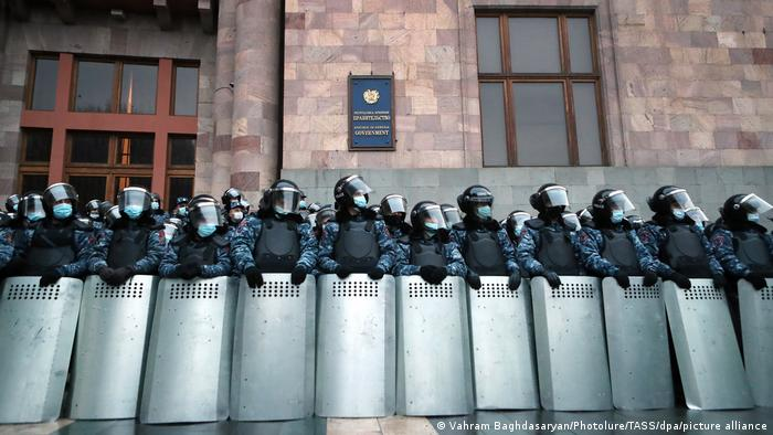 Law enforcement officers stand guard outside the offices of the Armenian Government