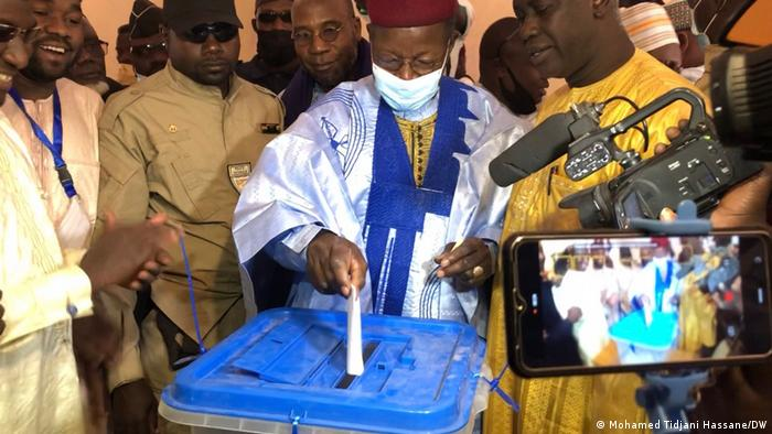 Oppositionskandidat Mahamane Ousmane steckt umstanden von anderen Männern seinen Stimmzettel in eine Wahlurne, Stimmabgabe bei der Wahl in Niger (21.02.2021)