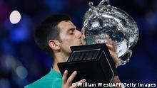 Serbia's Novak Djokovic kisses the Norman Brookes Challenge Cup trophy following his victory against Russia's Daniil Medvedev in their men's singles final match on day fourteen of the Australian Open tennis tournament in Melbourne on February 21, 2021. (Photo by William WEST / AFP) / -- IMAGE RESTRICTED TO EDITORIAL USE - STRICTLY NO COMMERCIAL USE -- (Photo by WILLIAM WEST/AFP via Getty Images)
