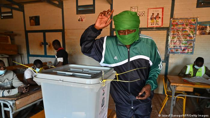 A man gestures after depositing his ballot in a sealed plastic container.