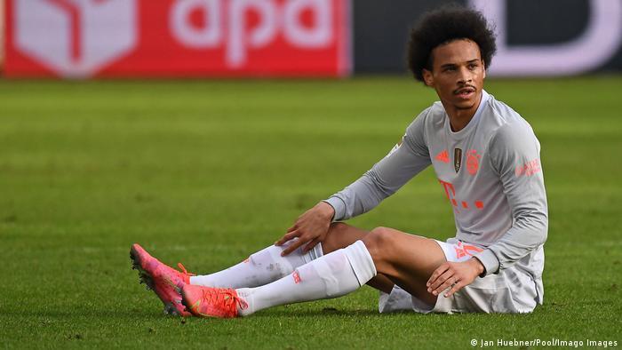 Bayern Munich's Leroy Sane sits on the turf in Frankfurt.