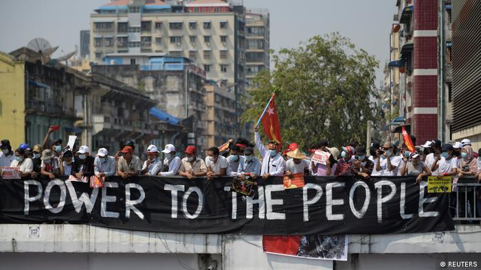Demonstrators standing behind a banner saying 'Power to the people' in Yangon, Myanmar