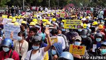 Protesters wearing hard hats and helmets display placards as they rally against the military coup in the northern town of Myitkyina